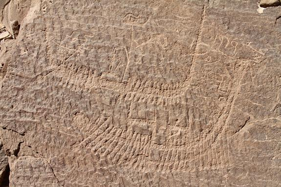 Look closely -- standing on the top of this boat is a crowned figure who may represent Narmer, the first pharaoh to rule unified Egypt. Oarsmen propel the boat along.