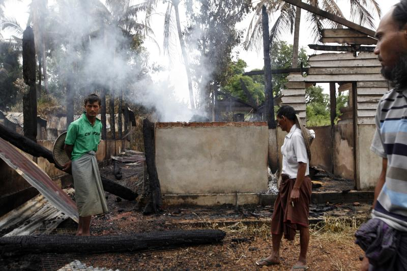 Muslims men stand by a burnt mosque which was destroyed during Tuesday's clashes between Buddhists and Muslims as smoke rises from debris in Thabyuchaing village, Thandwe township, Rakhine State, western Myanmar, Thursday, Oct. 3, 2013. Rakhine was home to much of the sectarian violence that has killed hundreds of people since June 2012. Violence that began Sunday in Rakhine's Thandwe township left five people dead, all of them Muslims, and at least 100 homes burned to the ground in three villages there, according to police Sgt. Aung Naing Win. He said at least one person was missing. (AP Photo/Khin Maung Win)