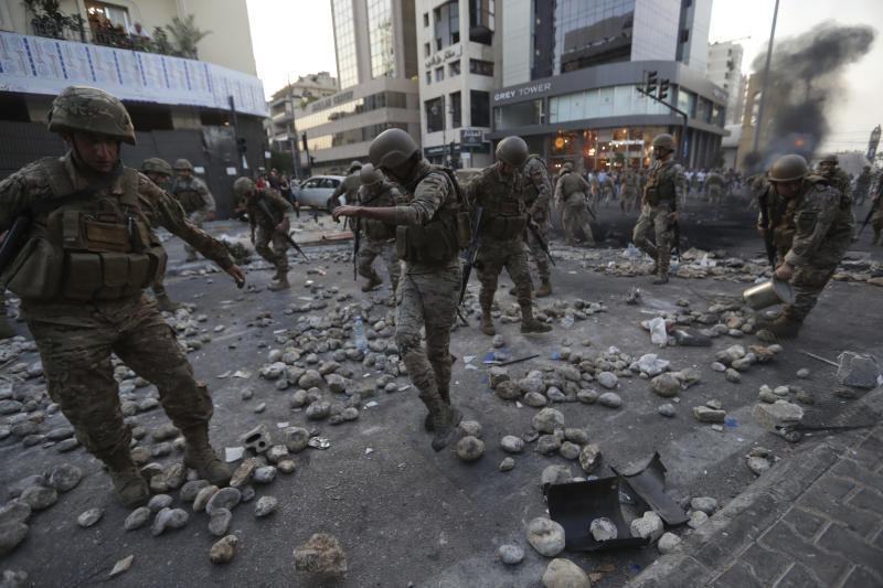 Lebanese soldiers open a road following scuffles between rival groups in the town of Jal el-Dib, north of Beirut, Lebanon, Wednesday, Nov. 13, 2019. A man opened fire over the heads of protesters in Jal el-Dib Wednesday, the second shooting incident in as many days as tensions rise in Lebanon between supporters and opponents of President Michel Aoun amid nationwide protests. (AP Photo/Hassan Ammar)