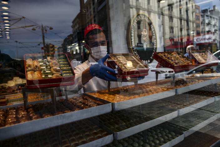 A worker prepares traditional Turkish sweets in a restaurant, in Istanbul, Tuesday, April 13, 2021. As Muslims around the world began marking Ramadan Tuesday, in mostly-Muslim Turkey, the month of fasting kicked off with some restrictions amid record levels of COVID-19 infections. (AP Photo/Emrah Gurel)