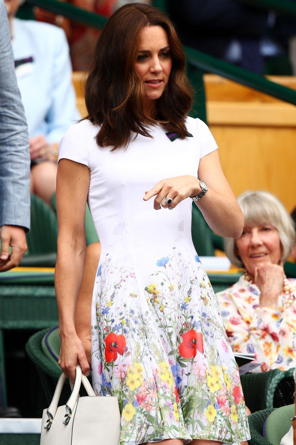 <p>In a Catherine Walker & Co colorful floral print dress and matching white bag while attending Wimbledon. </p>