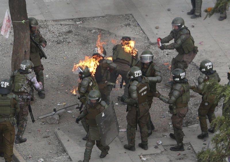 Police scramble after being hit with a gasoline bomb thrown by protesters during an anti-government protest in Santiago, Chile, Monday, Nov. 4, 2019. Chile has been facing weeks of unrest, triggered by a relatively minor increase in subway fares. The protests have shaken a nation noted for economic stability over the past decades, which has seen steadily declining poverty despite persistent high rates of inequality. (AP Photo/Esteban Felix)