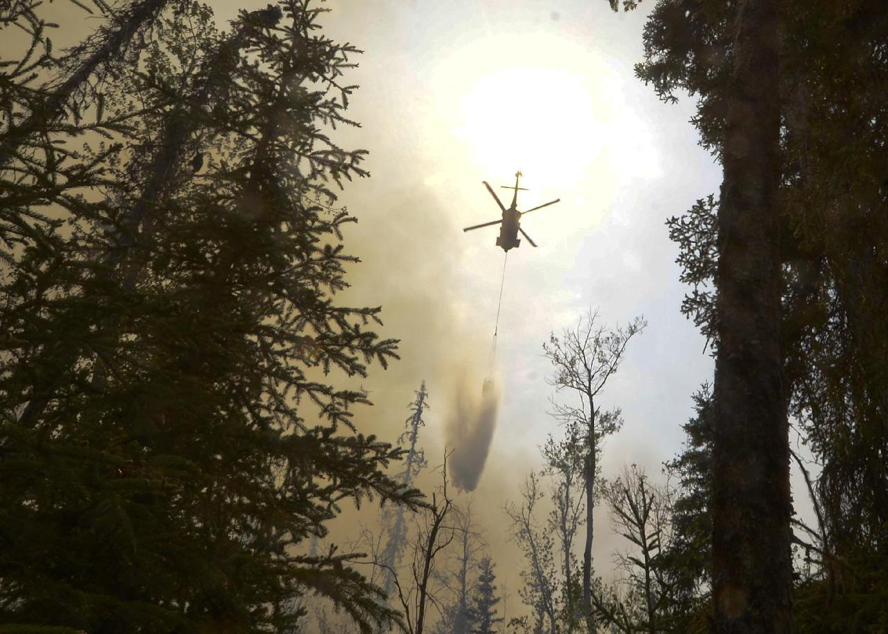 A helicopter dumps water on a portion of the Funny River Fire, Sunday, May 25, 2014, in the Funny River community in Soldotna, Alaska. The wildfire that has spread through the forest of Alaska's Kenai Peninsula has expanded in size, prompting authorities to order the evacuation of 1,000 structures, officials said. (AP Photo/Peninsula Clarion, Rashah McChesney)