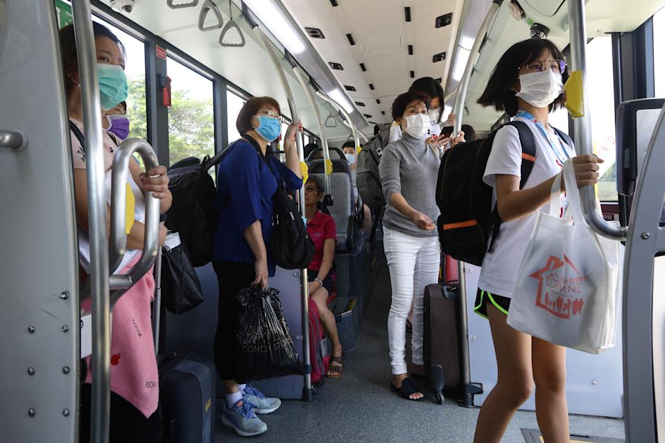 People wearing protective masks are seen inside a public bus after crossing from Johor Bahru, Malaysia on 17 March, 2020, in Singapore. (PHOTO: Getty Images)