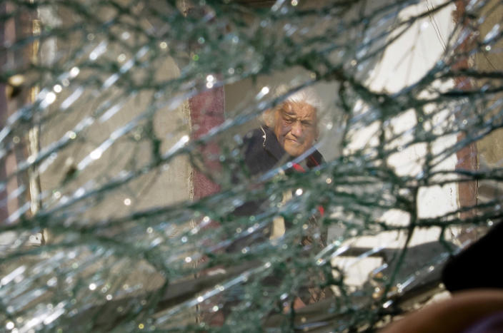 In this photo taken through a broken windshield of a car damaged by shelling by Azerbaijan's artillery, Raya Meropyan, 88 stands near her house in Stepanakert, the separatist region of Nagorno-Karabakh, Tuesday, Nov. 3, 2020. Fighting over the separatist territory of Nagorno-Karabakh entered sixth week on Sunday, with Armenian and Azerbaijani forces blaming each other for new attacks. (AP Photo)