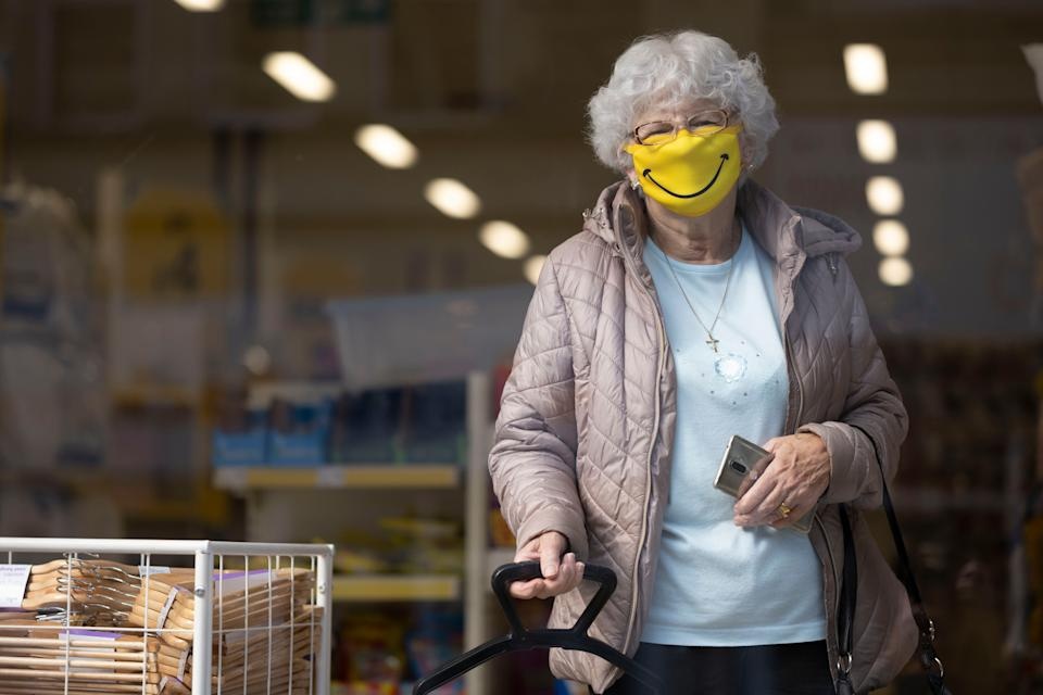A woman smiles while wearing a novelty face mask in a shop on October 1, 2020 in Barry, Wales (Photo: Matthew Horwood via Getty Images)