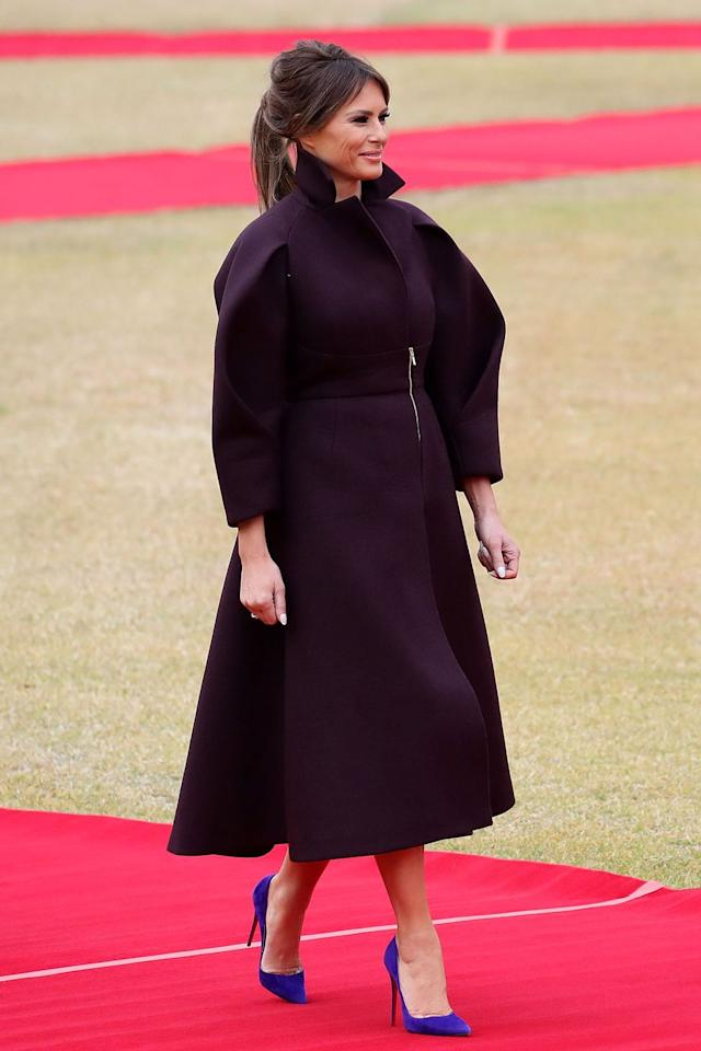 "<p>Arriving in South Korea, FLOTUS wore a deep burgundy Delpozo coat dress paired with blue-violet stiletto pumps. Look familiar? She wore a bright fuchsia dress from the brand in a similar silhouette for her <a href=""https://www.townandcountrymag.com/society/politics/a12444274/melania-trump-united-nations-speech/"" target=""_blank"">United Nations speech</a> back in September.</p>"