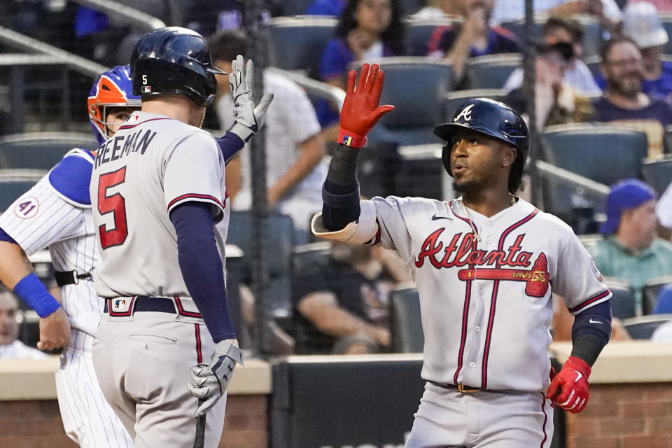 Atlanta Braves' Ozzie Albies, right, celebrates with Freddie Freeman after hitting a two-run home run during the second inning of the team's baseball game against the New York Mets, Tuesday, July 27, 2021, in New York. (AP Photo/Mary Altaffer)