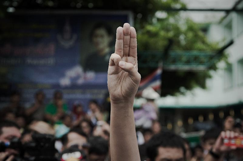 A supporter of anti-coup activists raises a three-finger salute outside a police station in Bangkok on June 24, 2015 (AFP Photo/Nicolas Asfouri)