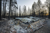 FILE - In this July 21, 2021 ,file photo, a home destroyed by the Bootleg Fire is seen near Bly, Ore. Each year thousands of acres of dense timber are thinned near remote communities, all designed to slow the spread of massive wildfires. While most scientific studies find such forest management is a valuable tool, environmental advocates say data from recent gigantic wildfires support their long-running assertion that efforts to slow wildfires have instead accelerated their spread. (AP Photo/Nathan Howard,File)