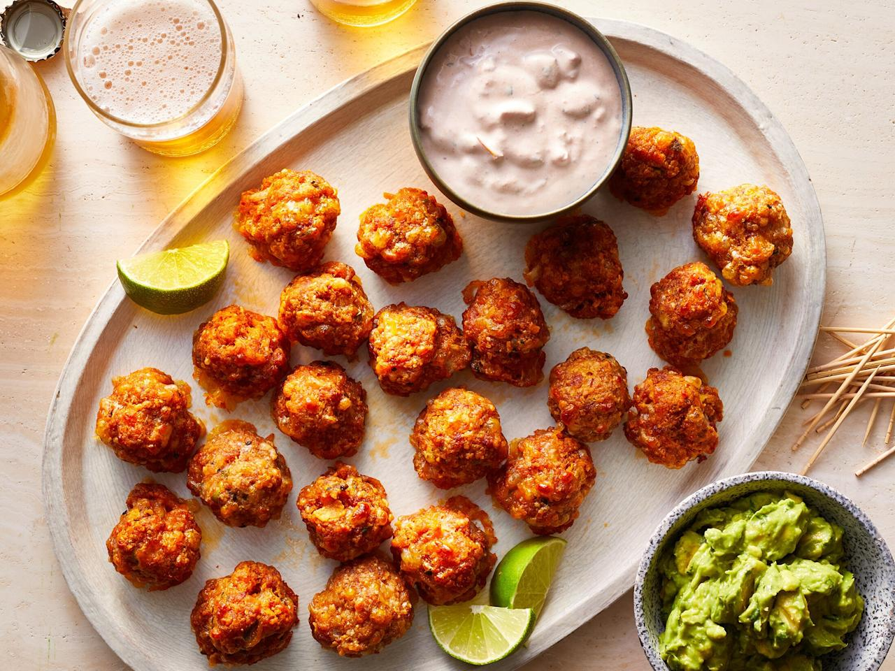 "<p>Nothing says <i>PARTY</i> like two of the all-time <a href=""https://www.myrecipes.com/course/appetizer-recipes/fast-finger-foods"">greatest finger foods </a>uniting as one. And that is exactly what is happening with these Nacho Sausage Balls. Adding chorizo, Mexican cheese, pickled jalapeño, cilantro, and crushed nacho cheese flavored Doritos to the mix gives <a href=""https://www.myrecipes.com/recipe/best-sausage-balls"">traditional sausage balls</a> a hit of spicy personality. They're perfect for <a href=""https://www.myrecipes.com/menus/best-tailgating-recipes"">tailgating</a> or <a href=""https://www.myrecipes.com/holidays-and-occasions/christmas-recipes/christmas-appetizers-recipes"">holiday parties</a>—plus, these next-level sausage balls can be made ahead of time and frozen for up to 1 month. For ease, form the sausage ball and freeze them in a single layer on a baking sheet; once frozen, transfer them to a freezer-safe container. When you're ready to serve, pop them straight from the freezer to the oven and bake for 30-35 minutes. Serve your nacho sausage balls with favorite nacho condiments, like sour cream, salsa, and <a href=""https://www.myrecipes.com/recipe/guacamole-14"">guacamole</a>, for dipping. </p> <p><a href=""https://www.myrecipes.com/recipe/nacho-sausage-balls"">Nacho Sausage Balls Recipe</a></p>"