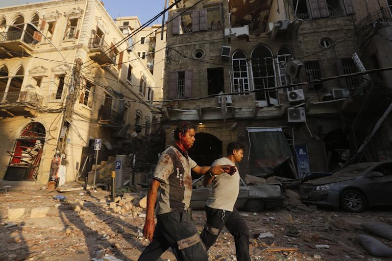 A wounded man is helped as he walks through debris in Beirut's Gemmayzeh district Tuesday. (Photo: MARWAN TAHTAH/AFP via Getty Images)