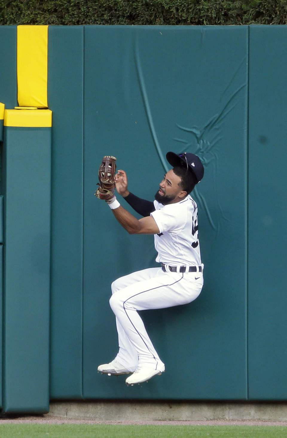 Detroit Tigers center fielder Derek Hill falls back to the ground after making a leaping catch of a fly ball hit by Seattle Mariners' Kyle Seager during the first inning of a baseball game Wednesday, June 9, 2021, in Detroit. Hill left the game with an injury. (AP Photo/Duane Burleson)