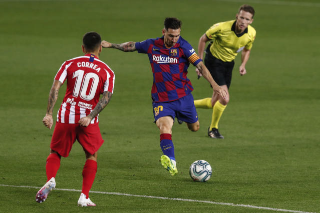Barcelona's Lionel Messi, center, kicks the ball in front Atletico Madrid's Angel Correa during the Spanish La Liga soccer match between FC Barcelona and Atletico Madrid at the Camp Nou stadium in Barcelona, Spain, Tuesday, June 30, 2020. (AP Photo/Joan Monfort)