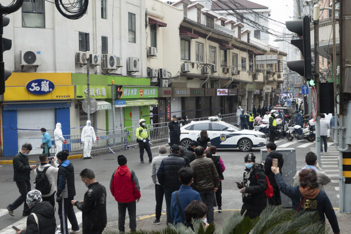 Bystanders watch as police officers and workers in protective suits close off a neighborhood as it is placed under lockdown in Shanghai, China, Thursday, Jan. 21, 2021. Shanghai has imposed lockdowns on two of China's best-known hospitals and some surrounding residential communities after they were linked to new coronavirus cases. (Chinatopix via AP)