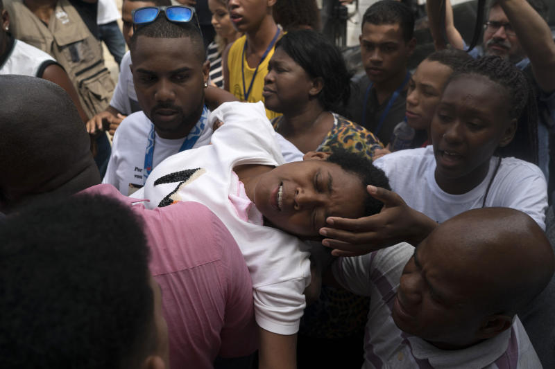 The mother of Samuel de Souza Rosa, one of the 10 young soccer players killed in a fire at the training ground of Brazilian soccer club Flamengo, is carried by mourners during his funeral in Sao Joao de Meriti, Brazil, Monday, Feb. 11, 2019. The death of de Souza Rosa and his teammates has shed a tragic light on the state of shoddy infrastructure and lax oversight in Latin America's largest nation. (AP Photo/Leo Correa)