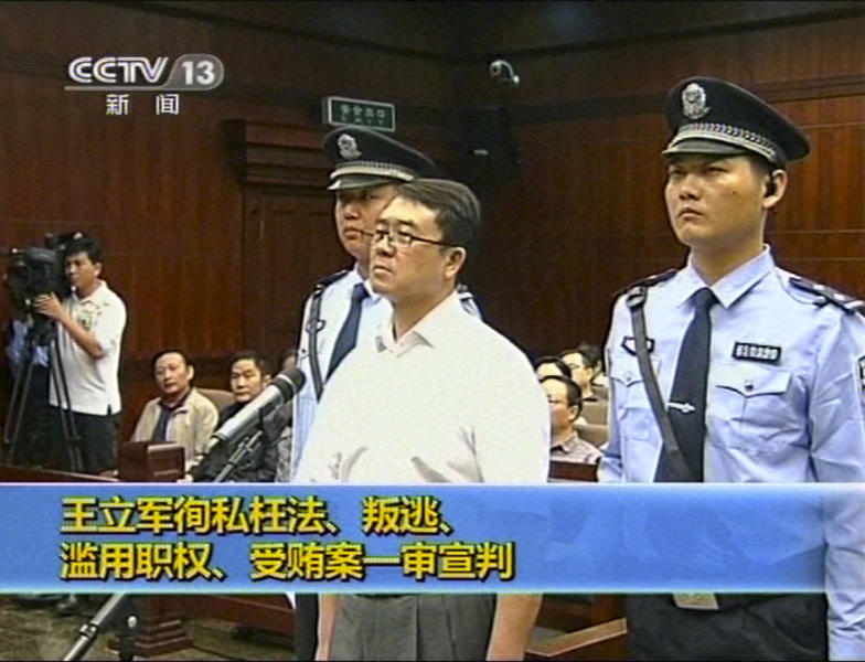 In this Sept. 24, 2012 video image taken from CCTV, Wang Lijun, center, stands while the verdict is announced during his trial at the Intermediate People's Court in Chengdu, in southwestern China's Sichuan province. The Chinese police chief whose thwarted defection exposed murder and infighting in high places was sentenced to 15 years in prison Monday, Sept. 24, 2012, setting the stage for China's leadership to close out the divisive scandal and move ahead with a generational handover of power. (AP Photo/CCTV via AP video) CHINA OUT, TV OUT
