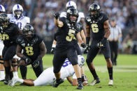 In this photo taken on Saturday, Sept. 14, 2019, Purdue defensive end George Karlaftis (5) celebrates a tackle against TCU during the first half of an NCAA college football game in West Lafayette, Ind. With 6-3, 325-pound Lorenzo Neal manning the middle and freshman All-American George Karlaftis back at defensive end, the Boilermakers defense should be stingier than the last year's unit. (AP Photo/Michael Conroy)