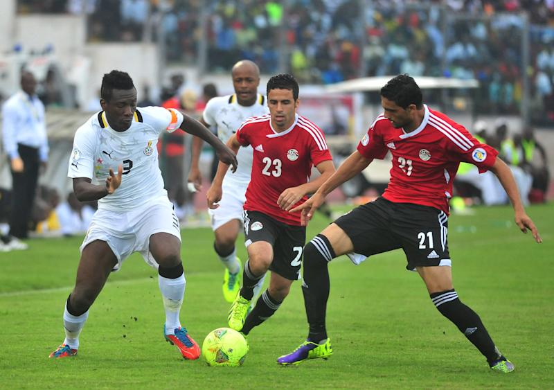 Ghana's Asamoah Gyan, left, battles with Egypt's Mohamed Naguib and Ahmed Shedid, right, during their World Cup playoff soccer match in Kumasi, Ghana, Tuesday, Oct. 15, 2013. Ghana stunned Egypt 6-1 in the first leg of their World Cup playoff on Tuesday, with Gyan's fifth-minute goal kicking off a dominant performance that makes the Black Stars overwhelming favorites to be one of the five African teams in Brazil next year. (AP Photo)