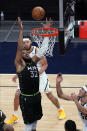 Minnesota Timberwolves' Karl-Anthony Towns (32) reaches for a rebound as Denver Nuggets' JaVale McGee, back, and Aaron Gordon watch during the first half of an NBA basketball game Thursday, May 13, 2021, in Minneapolis. (AP Photo/Jim Mone)