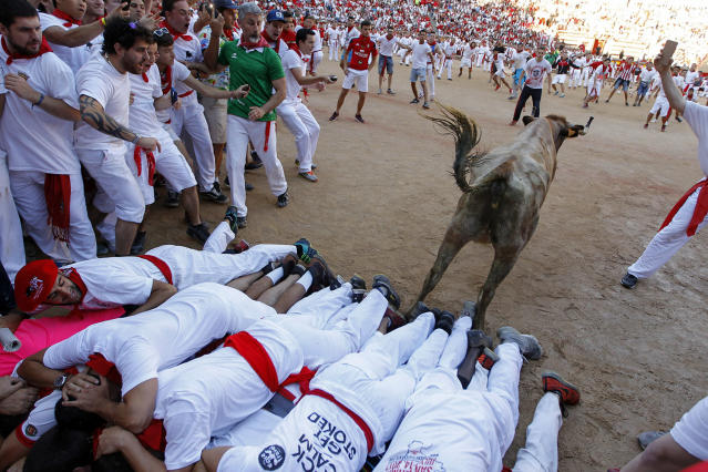 <p>A cow jumps over a group of revellers laid on the ground of the bullring, during the running of the bulls at the San Fermin Festival, in Pamplona, northern Spain, July 12, 2017. Revellers from around the world flock to Pamplona every year to take part in the eight days of the running of the bulls. (Photo: Alvaro Barrientos/AP) </p>