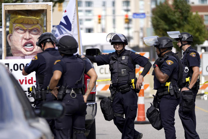 Cleveland Police officers surround a vehicle that approached the perimeter outside the Health Education Campus of Case Western Reserve University, where Republican candidate President Donald Trump and Democratic candidate former Vice President Joe Biden are set to have their first debate, Monday, Sept. 28, 2020, in Cleveland. (AP Photo/Julio Cortez)