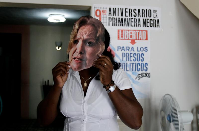 Berta Soler, leader of the Cuban dissident group Ladies in White, holds a mask of Laura Pollan up to her face, after being freed from detention in Havana, Cuba, Monday March 19, 2012. Soler and dozens of supporters of the Ladies in White were taken into custody early Sunday. Pollan is the group's former leader and co-founder who died in 2011 of a heart attack. (AP Photo/Franklin Reyes)