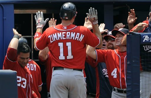 Washington Nationals' Ryan Zimmerman (11) is congratulated on his home run off the Atlanta Braves in the fifth inning of their baseball game, Sunday, July 1, 2012, at Turner Field in Atlanta. (AP Photo/David Tulis)