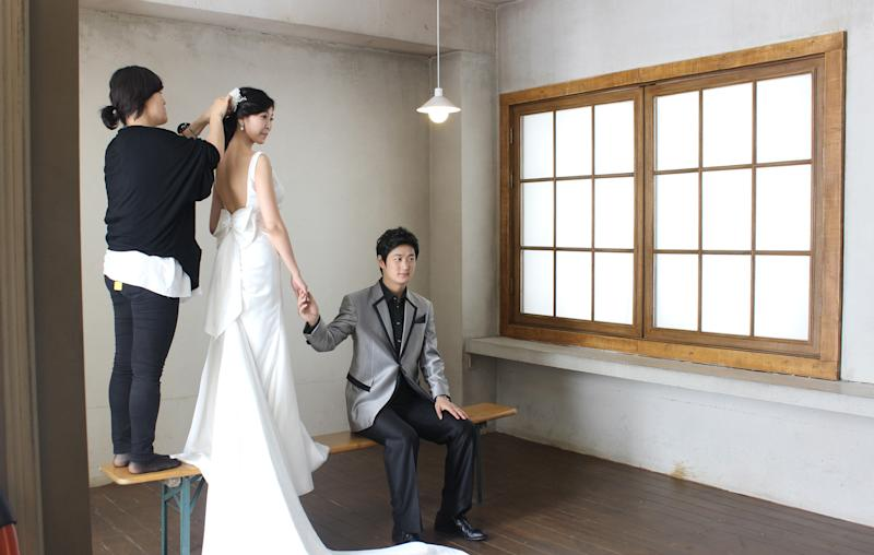 Chen Jingjing, right, and Yang Candi of Beijing, China, look for cues from their South Korean photographer as an assistant fixes Yang's hair ornament during an eight-hour wedding shoot Tuesday, July 30, 2013, at a wedding studio in southern Seoul, South Korea. China is the source of one quarter of all tourists to South Korea, and a handful of companies in South Korea's $15 billion wedding industry are wooing an image-conscious slice of the Chinese jet set happy to drop several thousand dollars on a wedding album with a South Korean touch. (AP Photo/Elizabeth Shim)