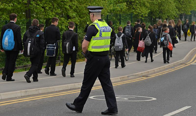 A police officer patrols as pupils (L) arrive for school at Corpus Christi Catholic College in Leeds, northern England on April 29, 2014, following the fatal stabbing of Spanish teacher Anne Maguire by a pupil Monday. Police arrested a 15-year-old male pupil after a female teacher was stabbed to death at a Catholic school in Britain on Monday. AFP PHOTO / PAUL ELLIS (Photo credit should read PAUL ELLIS/AFP via Getty Images)
