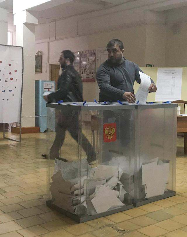 A voter casts a ballot at a polling station number 216 during the presidential election in Ust-Djeguta, Russia March 18, 2018. The voter declined to comment to Reuters reporter when asked why he was voting a second time, and left the building quickly. Picture taken March 18, 2018. REUTERS/Maria Tsvetkova