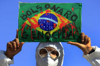 """FILE - In this May 26, 2021 file photo, a demonstrator holds an image of the Brazilian flag covered in fake blood and the Portuguese phrase """"Bolsonaro Genocide"""" during an anti-government protest by unions against President Jair Bolsonaro's policies to fight the COVID-19 pandemic in Brasilia, Brazil. Brazil's Senate is publicly investigating how the death toll got so high, focusing on why Bolsonaro's government ignored opportunities to buy vaccines for months. (AP Photo/Eraldo Peres, File)"""