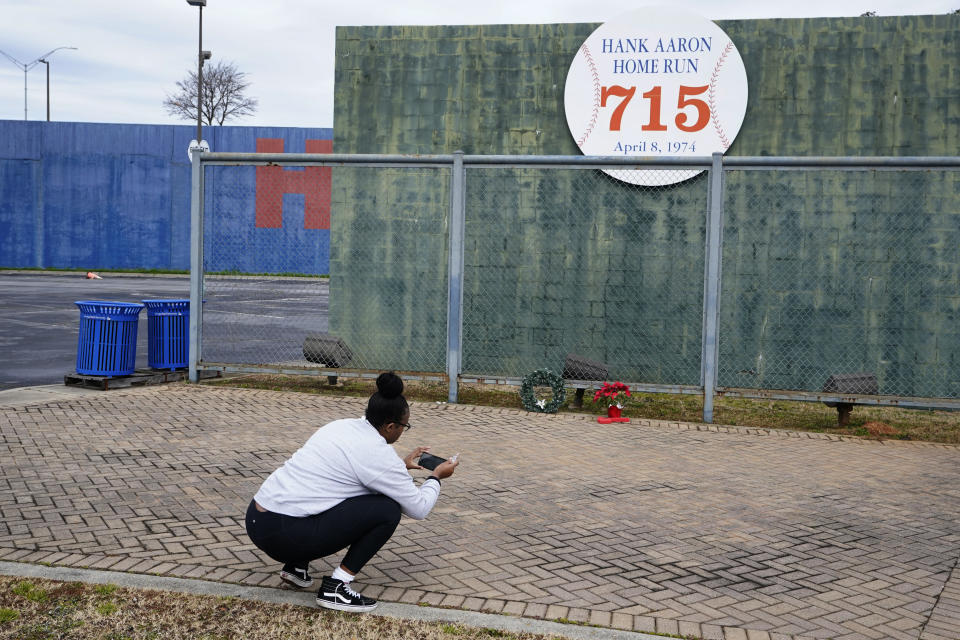 Krystal Dixon takes a photo in front of Hank Aaron's home run wall, left from when Atlanta's Fulton County Stadium was demolished, where Aaron hit his 715th home run on April 8, 1974 to break the career home run record held by Babe Ruth. Hank Aaron died Friday, Jan. 22, 2021. He was 86. (AP Photo/John Bazemore)