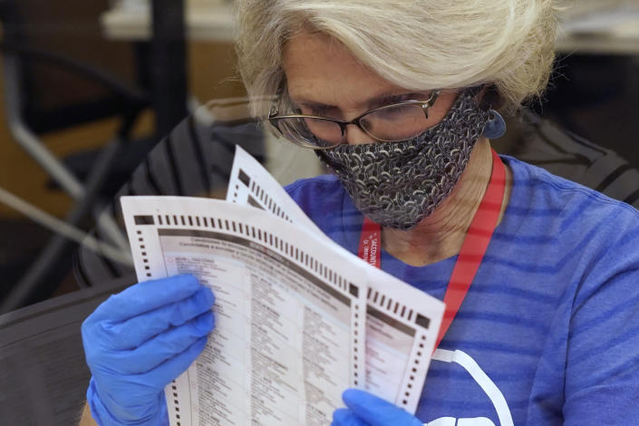 """FILE - In this Tuesday, Sept. 14, 2021, file photo, an election worker inspects a ballot for damage before they are sent to be tabulated at the Sacramento County Registrar of Voters Office in Sacramento, Calif. On Friday, Sept. 17, 2021, The Associated Press reported on stories circulating online incorrectly asserting there was fraud in California's recall election because voters were given Sharpie pens or other permanent markers, which the false posts said is illegal and will invalidate ballots. """"Sharpie pens are safe and reliable to use on ballots, and recommended due to their quick-drying ink,"""" reads a Nov. 5 statement from Dominion Voting Systems. """"Regarding potential ink bleed-through, Dominion's systems never allow for the creation of ballots with overlapping vote bubbles between the front and back pages of a ballot."""" (AP Photo/Rich Pedroncelli, File)"""
