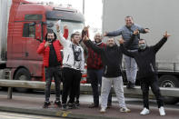 European truck drivers pose for a photograph as they wait for the port to reopen in Dover, the main ferry link between southern England and France, Tuesday, Dec. 22, 2020. Trucks waiting to get out of Britain backed up for miles and people are left stranded at airports as dozens of countries around the world slapped tough travel restrictions on the U.K. because of a new and seemingly more contagious strain of the coronavirus in England.(AP Photo/Kirsty Wigglesworth)