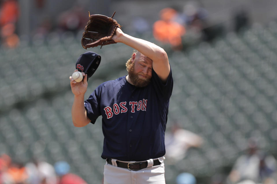 """Boston Red Sox starting pitcher Andrew Cashner wipes his forehead after allowing a home run to Baltimore Orioles' Trey Mancini in the first inning of a baseball game, Sunday, July 21, 2019, in Baltimore. The National Weather Service says the """"oppressive and dangerous"""" heat wave will abate by Monday and Tuesday. The agency says a swath of the East Coast, from the Carolinas up to Maine, faces the greatest heat threat Sunday. (AP Photo/Julio Cortez)"""