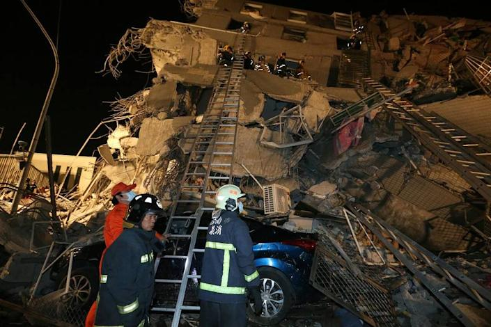 Rescue personnel search through debris at the site of a collapsed building in the southern Taiwanese city of Tainan following a strong 6.4-magnitude earthquake that struck the island early on February 6, 2016 (AFP Photo/)