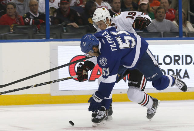Chicago Blackhawks center Jonathan Toews (19), of Canada, fights for possession with Tampa Bay Lightning center Valtteri Filppula (51), of Finland, during the first period of an NHL hockey game on Thursday, Oct. 24, 2013, in Tampa, Fla. (AP Photo/Reinhold Matay)