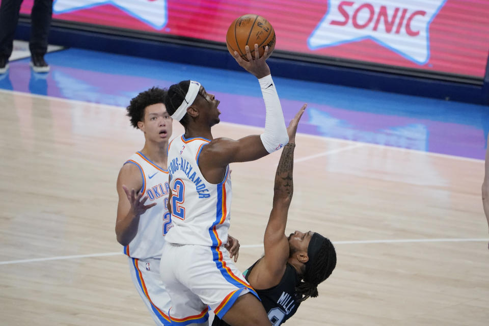 Oklahoma City Thunder guard Shai Gilgeous-Alexander (2) shoots over San Antonio Spurs guard Patty Mills, right, during the second half of an NBA basketball game Wednesday, Feb. 24, 2021, in Oklahoma City. (AP Photo/Sue Ogrocki)