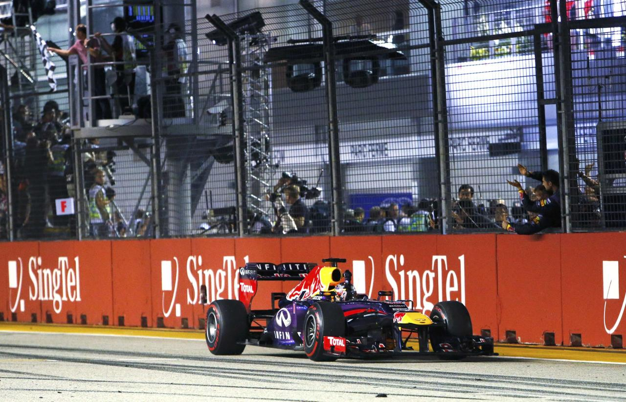 Red Bull Formula One driver Sebastian Vettel of Germany takes the chequered flag to win the Singapore F1 Grand Prix as team members cheer at the Marina Bay street circuit in Singapore September 22, 2013. Vettel cruised to a third straight Singapore Grand Prix victory on Sunday and moved closer to a fourth consecutive Formula One world title with a dominant drive under the floodlights at the Marina Bay Street Circuit. REUTERS/Edgar Su (SINGAPORE - Tags: SPORT MOTORSPORT F1)