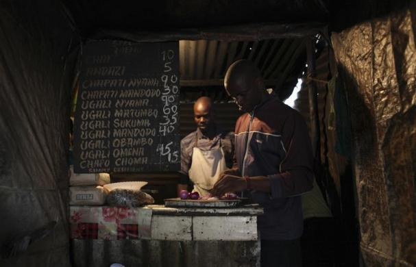 Denis Onyango Olang, (R), a 26 year-old assistant cook, prepares food in a dimly lit kitchen at a hotel in Nairobi's Kibera slum in the Kenyan capital, April 30, 2012. Onyango Olang studied statistics and chemistry at Jomo Kenyatta University of Agriculture and Technology where he received a degree in science. He has been searching for permanent employment for two years but has decided to make a living working in the slums for the last eight months.