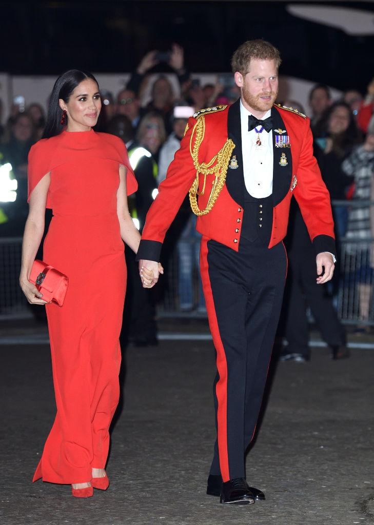 <p>The Duchess of Sussex wore a ruby red gown with cape detail for the Mountbatten Festival of Music at Royal Albert Hall in March 2020. Markle previously wore a turquoise version of the dress for a state dinner in Fiji. <em>(Image via Getty Images)</em></p>
