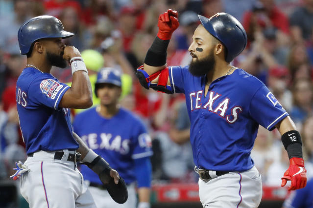 Texas Rangers' Rougned Odor, right, celebrates with Delino DeShields, left, after hitting a grand slam off Cincinnati Reds relief pitcher Wandy Peralta in the fifth inning of a baseball game, Friday, June 14, 2019, in Cincinnati. (AP Photo/John Minchillo)