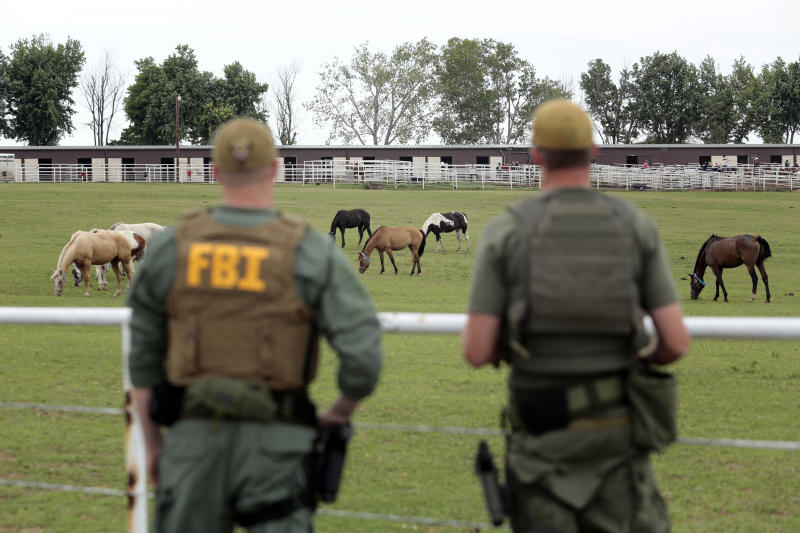 FBI agents overlook a horse ranch under investigation Tuesday, June 12, 2012 in Lexington, Okla. Federal agents raided the Oklahoma ranch and a prominent quarter horse track in New Mexico on Tuesday, alleging the brother of a high-ranking official in a Mexican drug cartel used a horse-breeding operation to launder money. (AP Photo/Brett Deering)