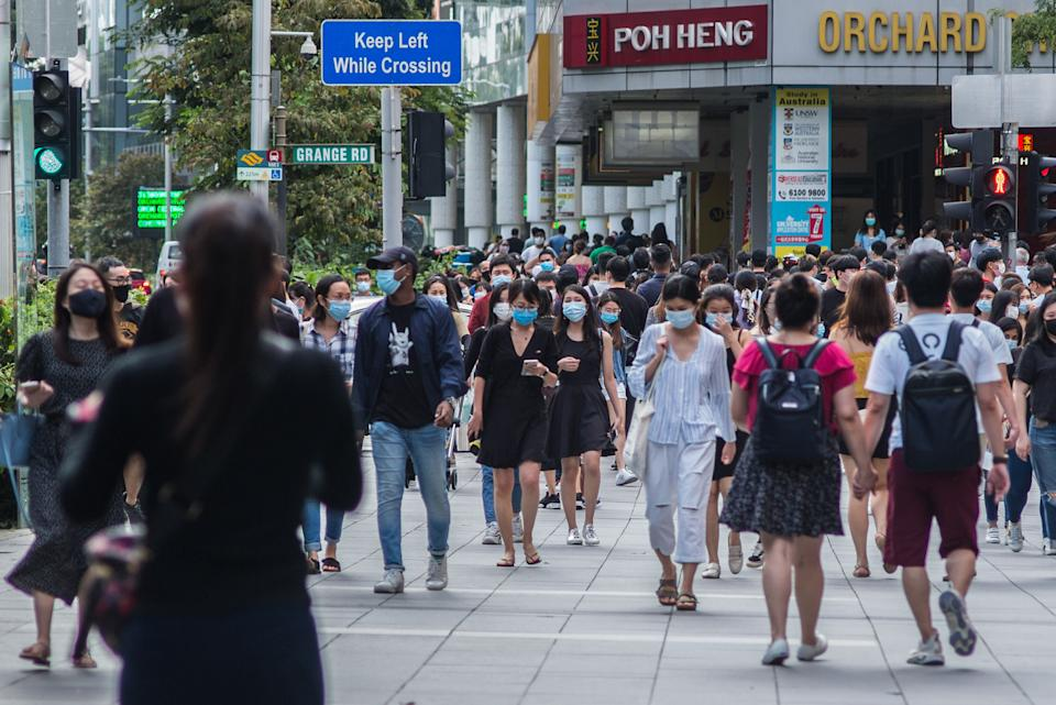 SINGAPORE - 2020/07/25: People wearing protective masks walk along Orchard Road, a famous shopping district in Singapore.  As of 26 July 2020, the total number of confirmed COVID-19 cases in Singapore are at 50,369. (Photo by Maverick Asio/SOPA Images/LightRocket via Getty Images)