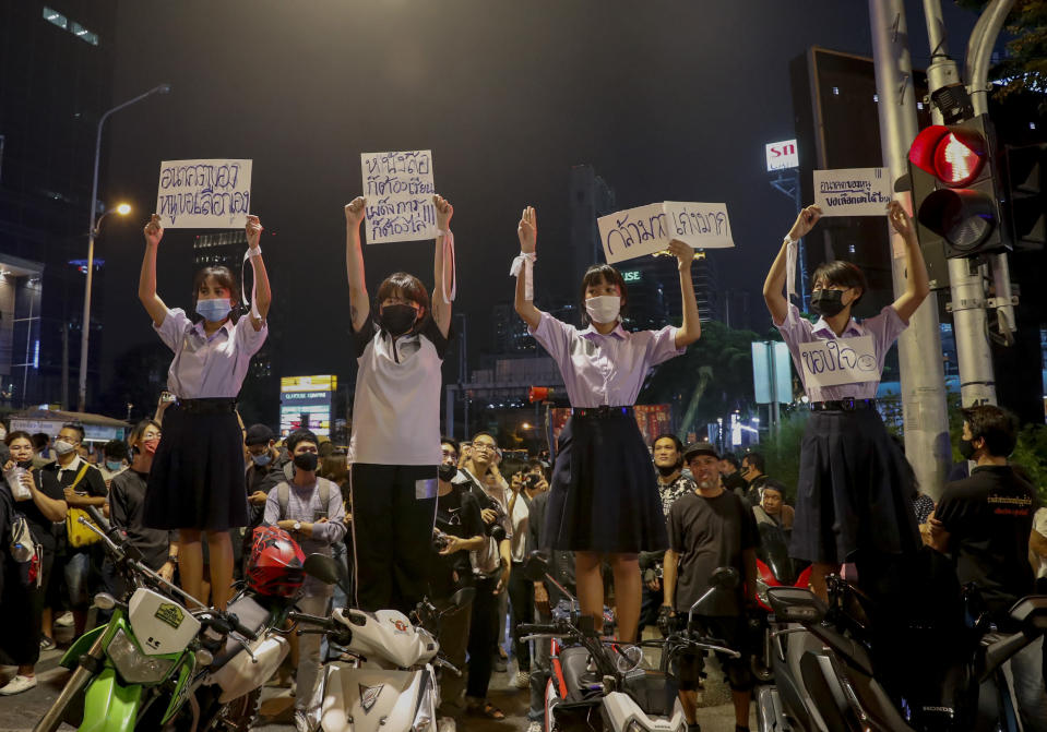 """School children and supporters of pro-democracy protesters, display placards during a rally at a major intersection next to the German Embassy in central Bangkok, Thailand Monday, Oct. 26, 2020. As lawmakers debated in a special session in Parliament that was called to address political tensions, the students-led rallies were set to continue with a march through central Bangkok Monday evening to the German Embassy, apparently to bring attention to the time King Maha Vajiralongkprn spends in Germany. Placards from left read: """"My future, can I choose it by myself, Have to study and disperse dictatorship at the same time, very brave, very good, Thank you."""" (AP Photo/Gemunu Amarasinghe)"""