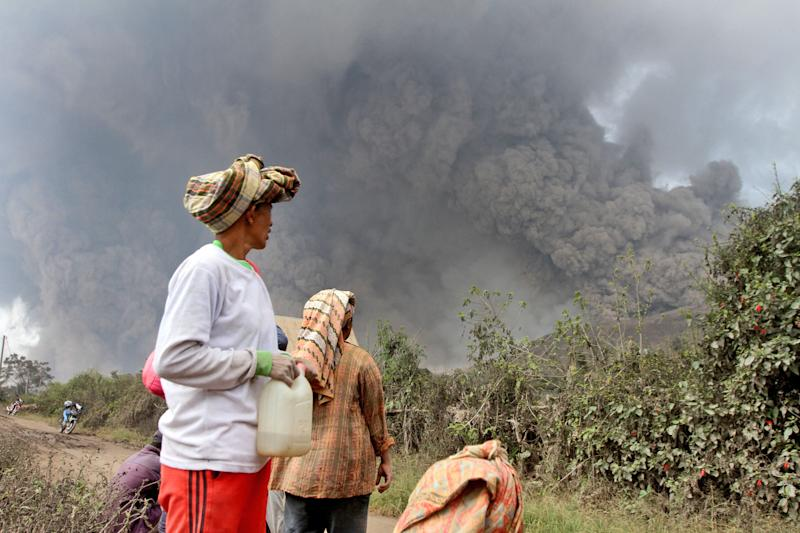 Villagers watch as Mount Sinabung releases pyroclastic flows during an eruption in Namantaran, North Sumatra, Indonesia, Saturday, Feb. 1, 2014. The rumbling volcano in western Indonesia has unleashed fresh clouds of searing gas, killing a number people and injuring few others. (AP Photo)