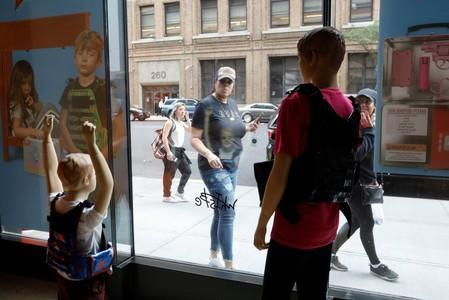 """People look at mannequins wearing bullet proof vests as part of an art installation by artist WhIsBe titled """"Back to School Shopping"""" to illustrate the dangers of gun violence in schools, at a gallery in New York City"""