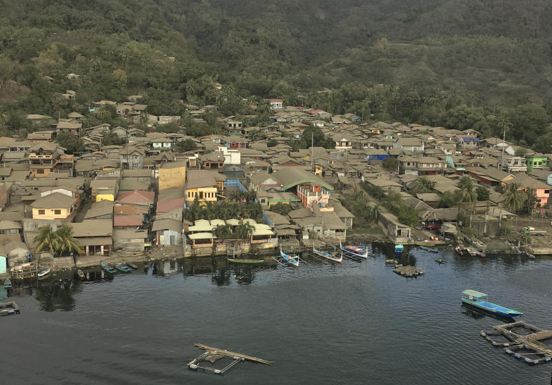 In this Jan. 21, 2020, photo provided by the Philippines Office of Civil Defense, volcanic ash covers roofs of houses near Taal volcano in Batangas province, southern Philippines. The Philippine government will no longer allow people to live on the crater-studded island that's home to the volcano. (Office of Civil Defense via AP)