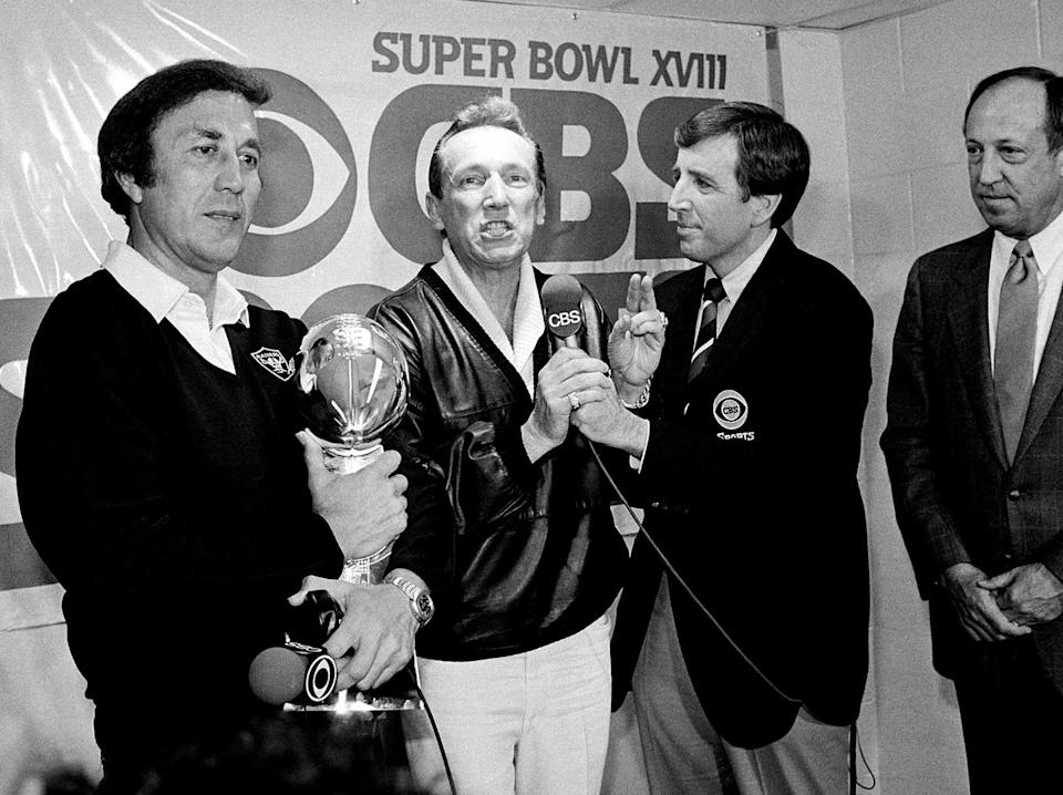 In this Jan. 23, 1984, file photo, Raiders coach Tom Flores clutches the Lombardi Trophy as team owner Al Davis is interviewed by Brent Musburger in the locker room after L.A.'s 38-9 victory over Washington in Super Bowl XVIII in Tampa, Florida. (AP Photo/File)